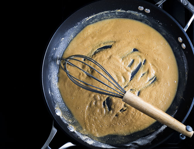 white roux being whisked in a skillet