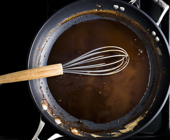 dark brown roux being whisked in a skillet