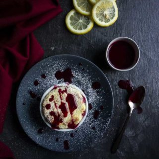 souffle drizzled with raspberry sauce on a plate with lemon slices in the background