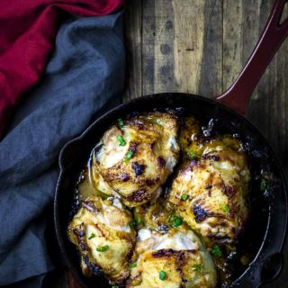 overhead view of roasted chicken thighs in a cast iron skillet garnished with green onions