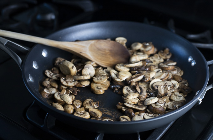 sauteed mushrooms in a skillet with a wooden spoon