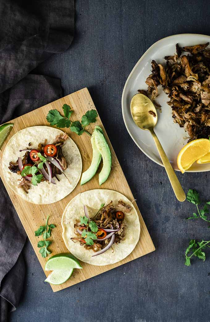 tacos on a board with a plate of shredded pork on the side
