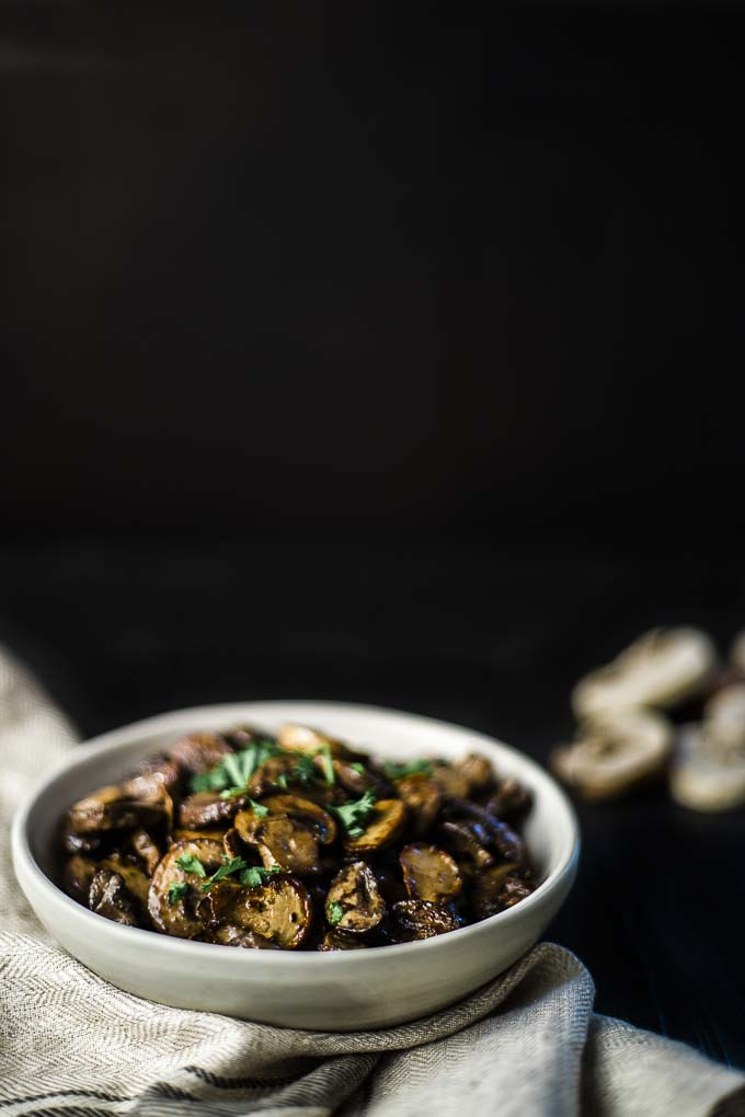 bowl of cooked mushrooms with parsley