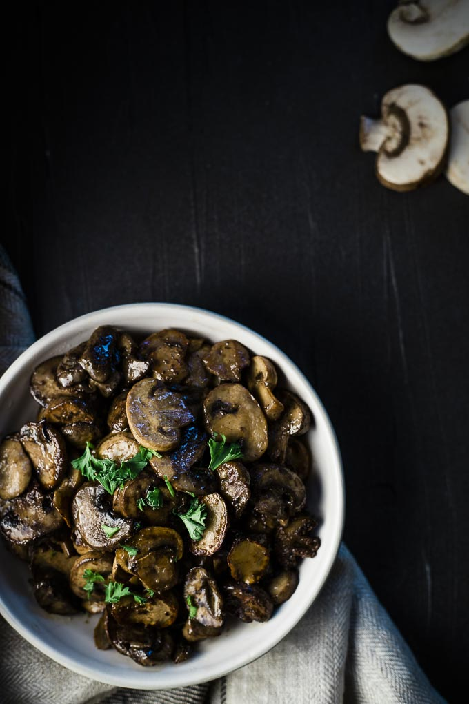 top down view of a bowl of sauteed mushrooms garnished with parsley