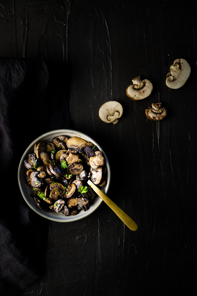owl of sauteed mushroom with a gold spoon