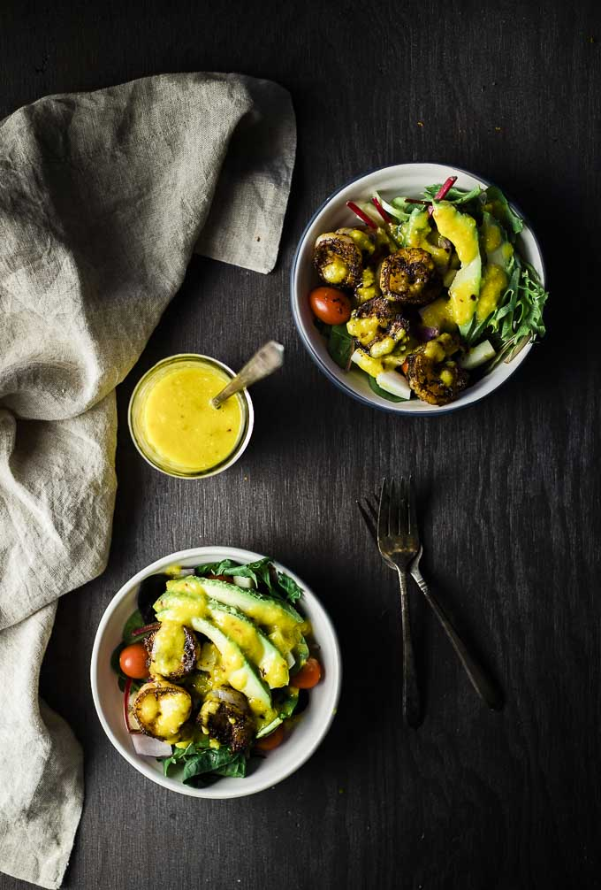 2 bowls of salad with shrimp, avocado, tomato and a jar of dressing with a spoon in between