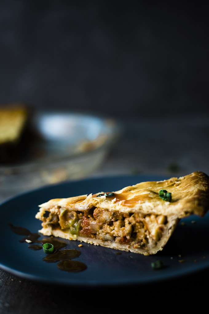 piece of crawfish pie garnished with green onions and hot sauce