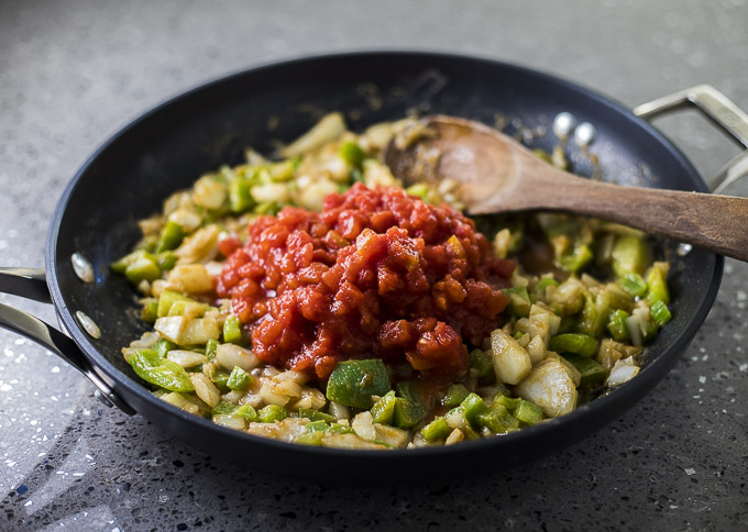 gren peppers, onions and tomatoes in a skillet