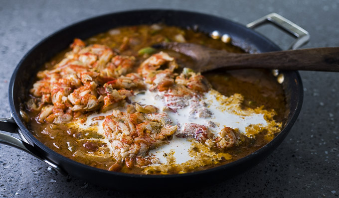 crawfish in a skillet with broth, cream and vegetables