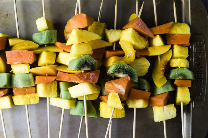 fruit on skewers on a baking sheet
