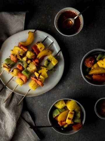 plate of fuirt kebabs with 2 bowls of fruit and chili