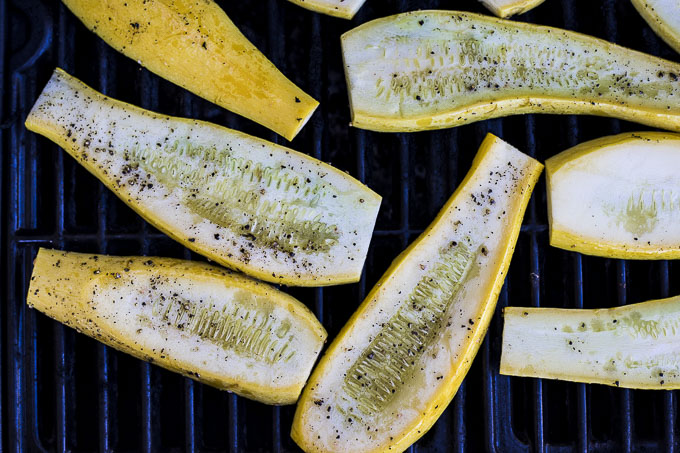 sliced yellow squash on a grill with salt and pepper
