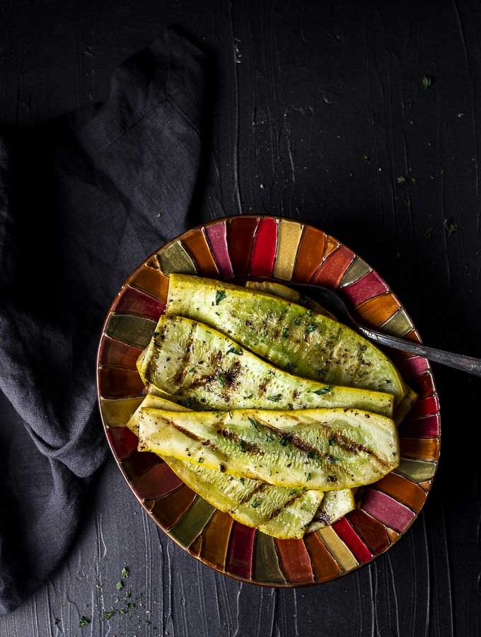 Grilled yellow squash in a bowl with a spoon