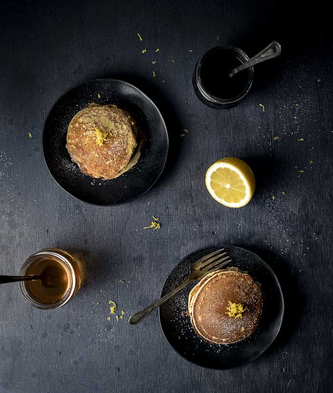 2 plates of pancakes topped with lemon zest