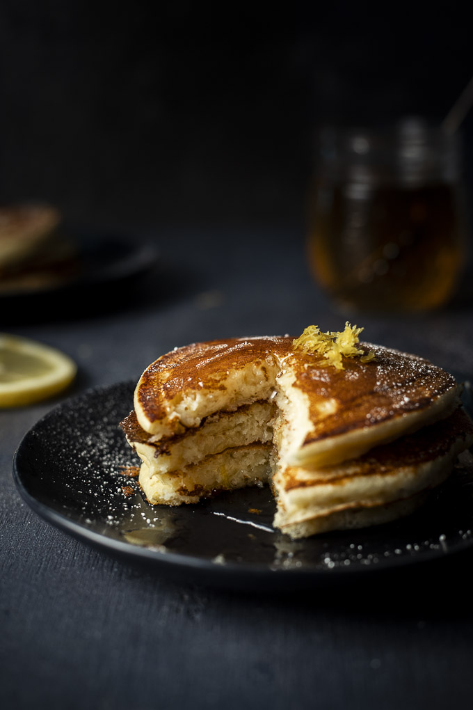 a plate of pancakes with a slice missing and drizzled in syrup
