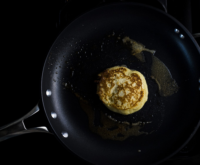 pancake cooking in a skillet with butter