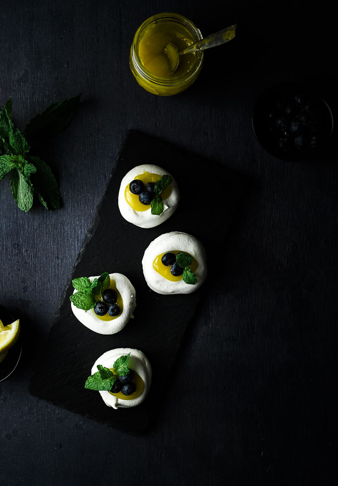 mini pavlovas on a plate with lemon and blueberries garnished with mint