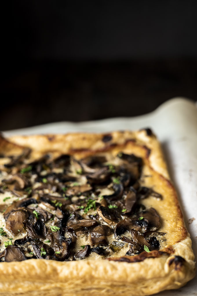 mushroom tart on parchment paper garnished with parsley