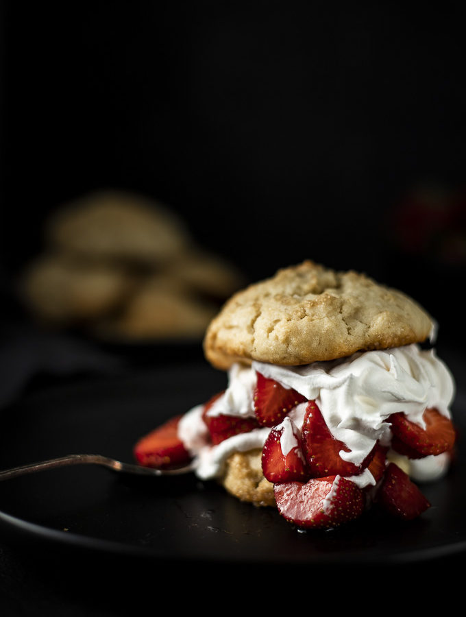 side view of strawberry shortcakes with whipped cream and 2 homemade shortcakebiscuits