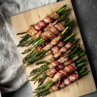 asparagus wrapped in bacon on a board