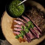 slices of flank steak drizzled in chimichurri (green sauce) with a bowl on the side