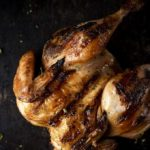grilled cornish game hen on a dark surface