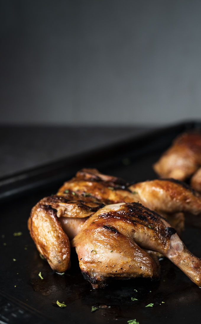 side view of grilled cornish game hen on a baking sheet