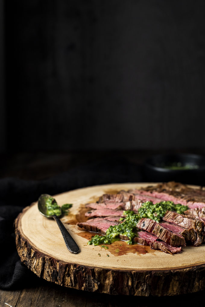 sliced steak with chimichurri sauce spooned over the top