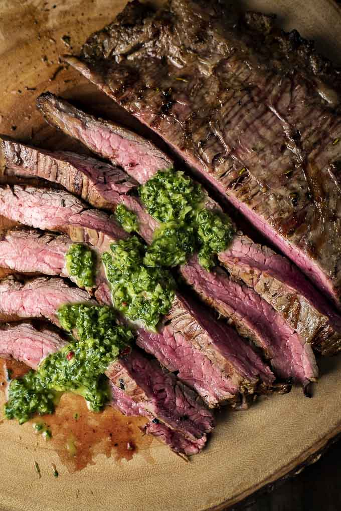 close up view of flank steak with green sauce