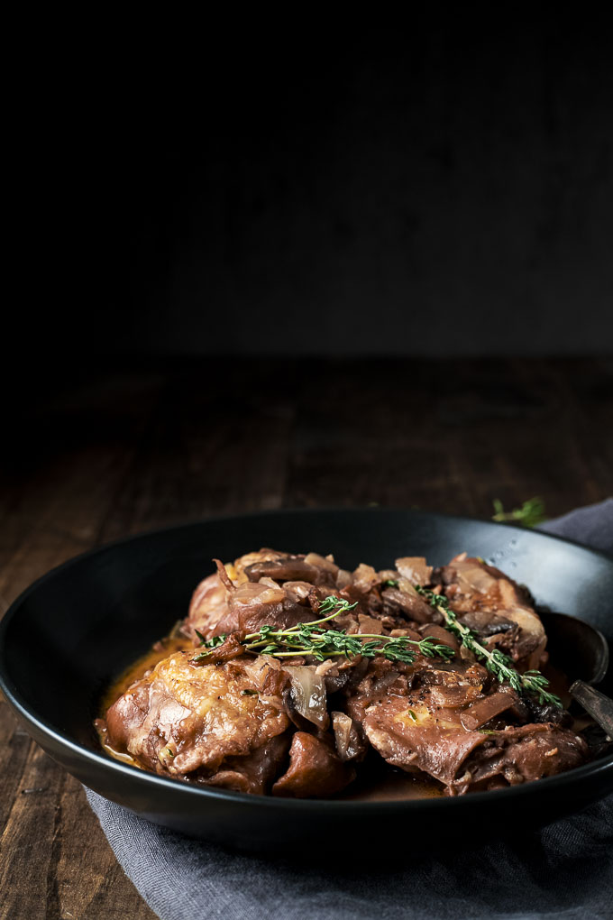 side view of chicken in a brown sauce garnished with herbs