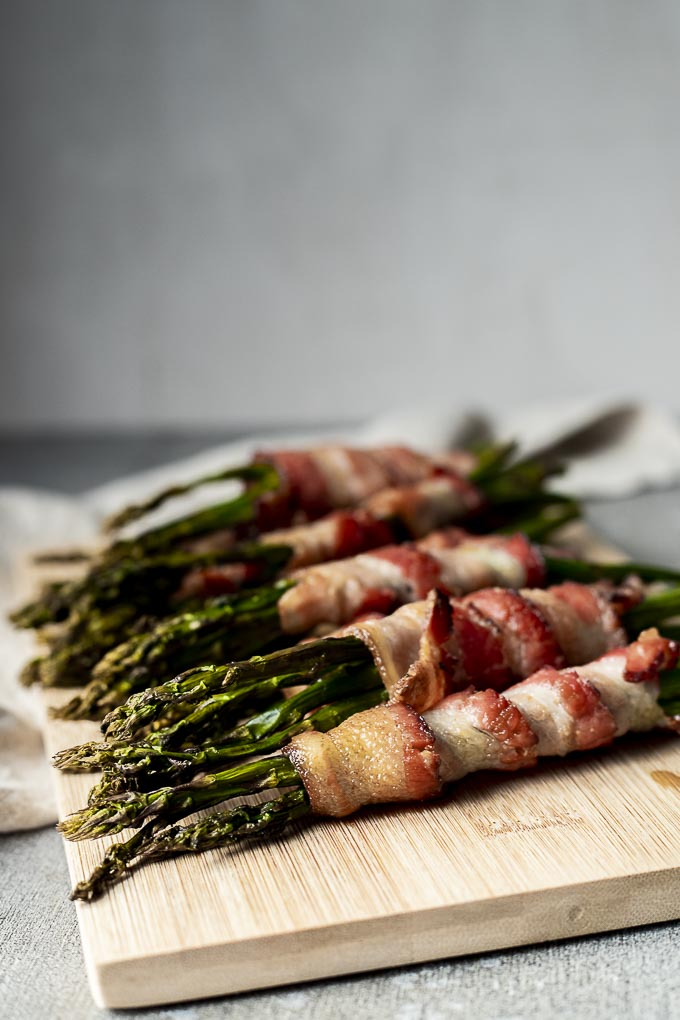 several pieces of asparagus wrapped in crispy bacon on a plate