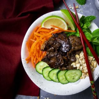 seared beef in a bowl with cucumbers, carrots, basil, peanuts and limes