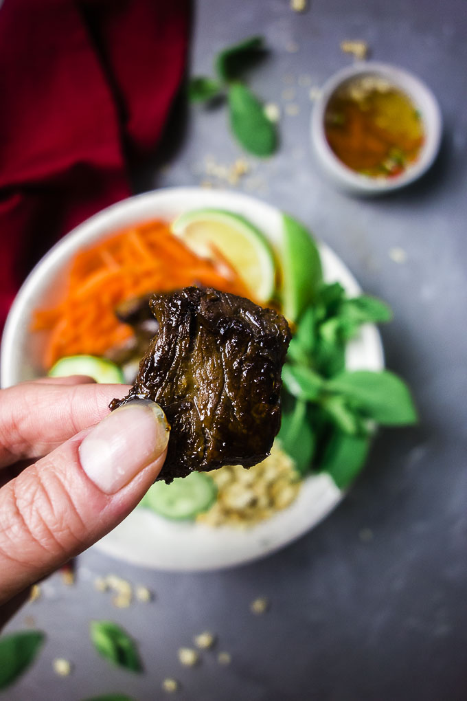 a piece of seared beef being held by fingers