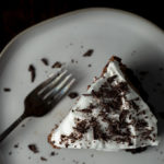 a piece of chocolate pie with whipped cream and shaved chocolate on a plate