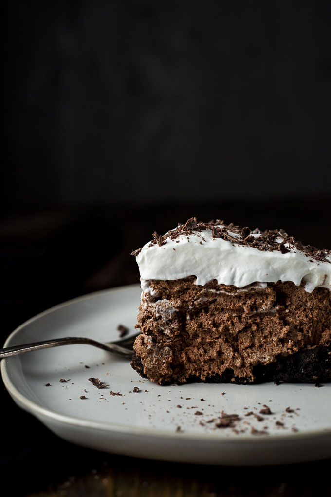 side view of a piece of chocolate mousse pie with whipped cream