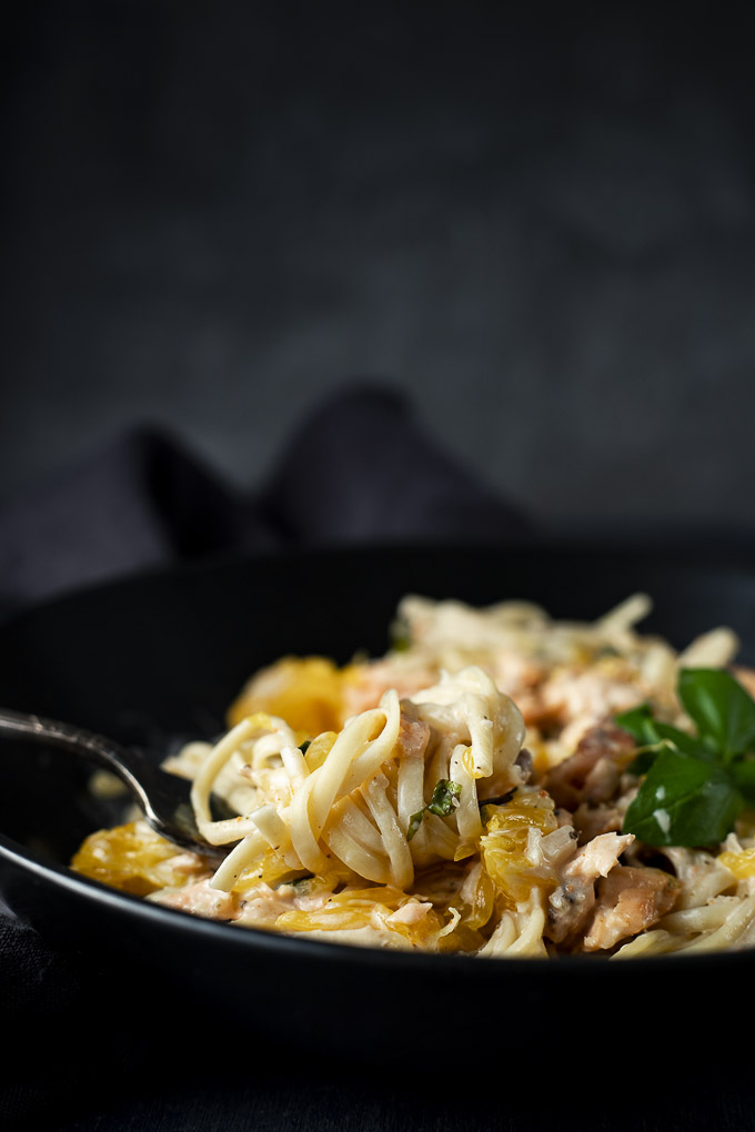 side view of forkful of creamy pasta in a bowl