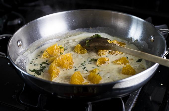 orange pieces in a creamy sauce in a saute pan