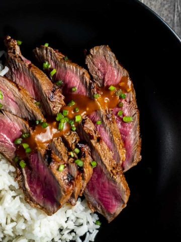 sliced beef cooked rare drizzled in orange sauce and chives