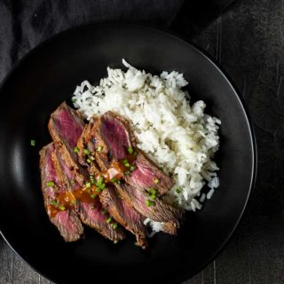 grilled beef slices and rice in a bowl with sauce and chives