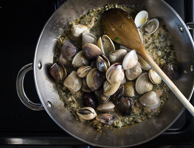 fresh clams with shells in a saute pan