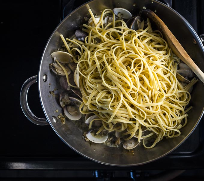 linguine on top of white clam sauce in a saute pan