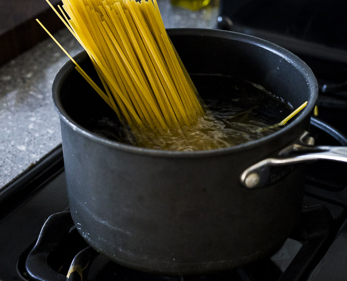dried linguine in a pot of boiling water
