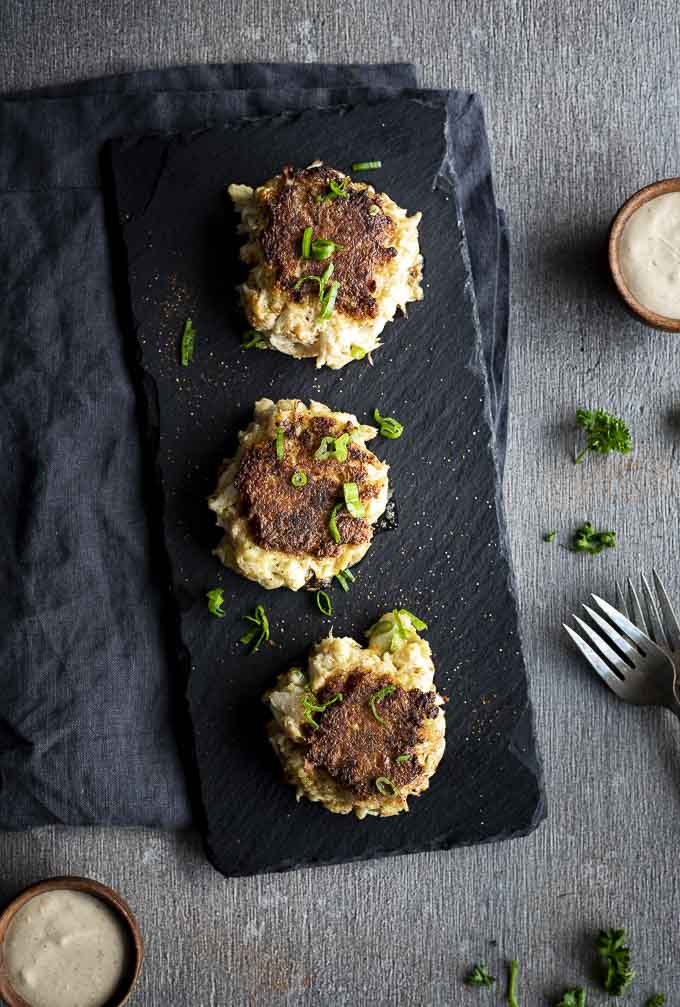 3 crabcakes on a serving platter with green onions on top - overhead view