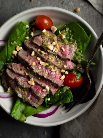 thai beef salad in a bowl with tomatoes and red onions