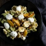 tortellini with peaches and ricotta cheese dollops in a bowl