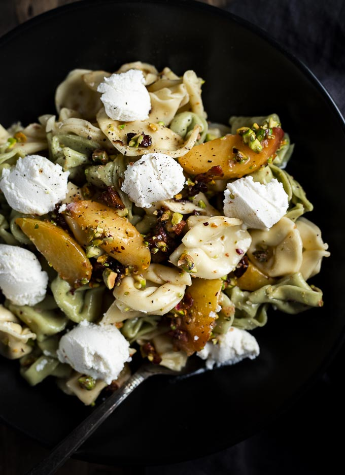 close up of tortellini pasta with peaches, pistachios and ricotta cheese