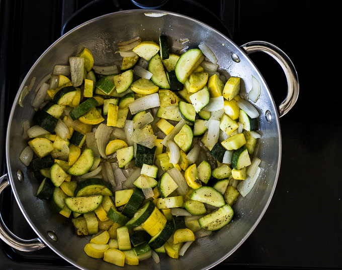 zucchini, squash and onions cooking in a skillet