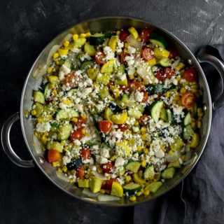 sauteed squash and vegetables sprinkled with cheese in a skillet