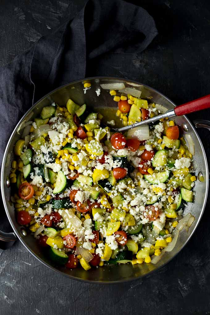 sauteed squash and vegetables sprinkled with cheese in a skillet with a spoon