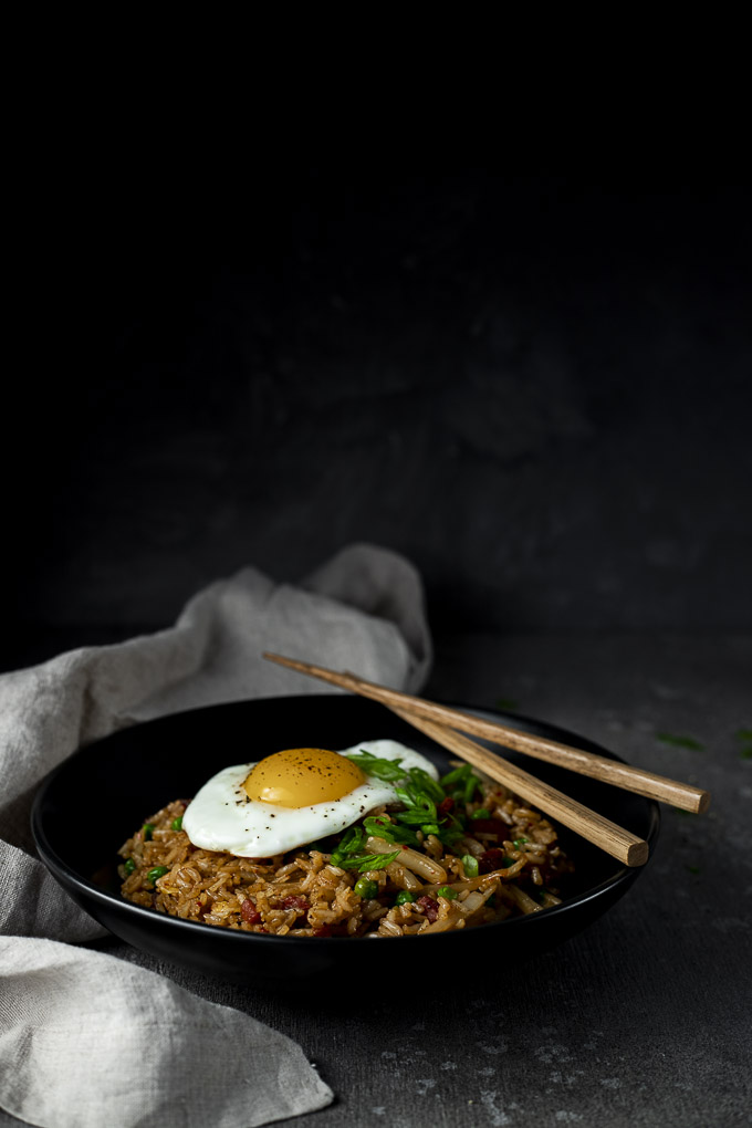 fried rice in a bowl with an egg and chopsticks